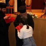 Ο Σεβασμιώτατος Μητροπολίτης Αιτωλίας και Ακαρνανίας κ. ΚΟΣΜΑΣ διανέμει αναμνηστικά στα παιδιά των χορωδιών